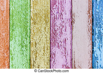 Colored flaky paint on a old weathered wooden fence. Vintage wood background.