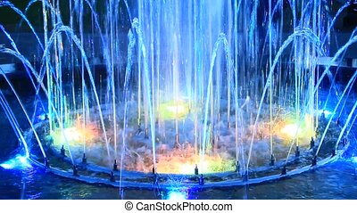 Colored fountains in city park. Colorful jets of water....