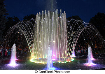 colored fountains in city park in the night