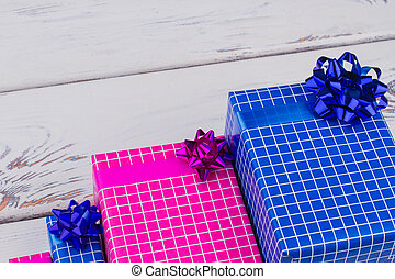 Colored gift boxes with bow on wooden background.