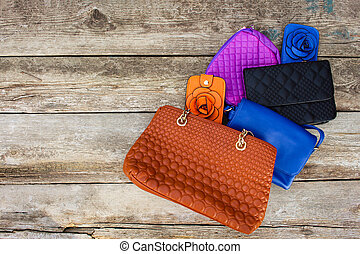Colored handbags on wooden background. Top view.