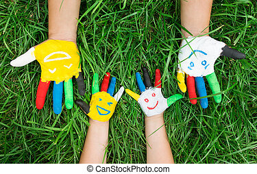Colored hands with smile painted in colorful paints against green summer background. Lifestyle concept