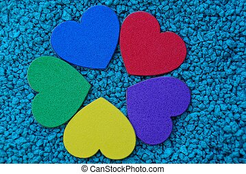 colored hearts on blue fine quartz sand