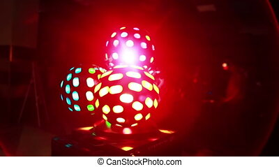 Colored light show in the dark at party. Close-up view of colored light balls twisting, shyning at disco club.