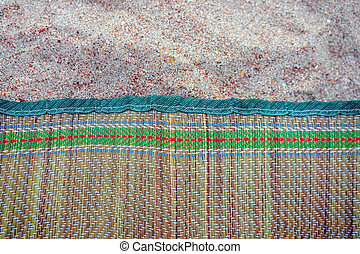 colored Mat on the beach sand as a background