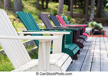 colored Muskoka chairs on the dock - a row of Muskoka chairs...