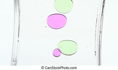 Colored oil. Time period. White. Close up - Hourglass with...
