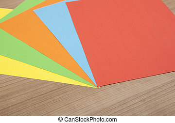 colored paper on wooden background