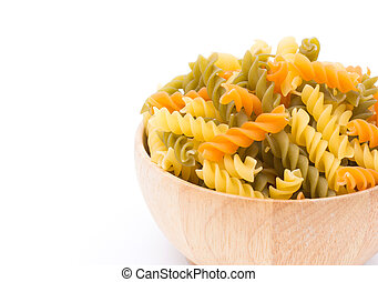 Colored pasta fusilli in a wooden bowl on white background