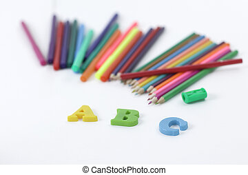 colored pencils and letters of the alphabet on a white background .photo with copy space