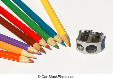Colored pencils and sharpener on white background