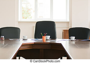 Colored pencils and three cups of coffee on the background of the three chairs in an office conference room
