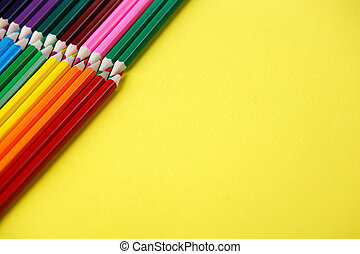 Colored pencils angle. Many different colored pencils on yellow background