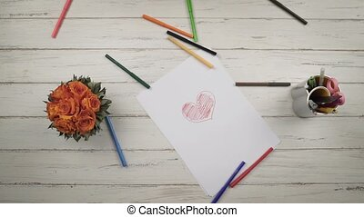Colored pencils fall on a stylish white wooden table. Clow mo. Top view. Hands close up view. St. Valentine's Day