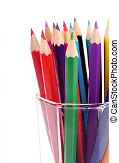 colored pencils in a glass beaker on a white background