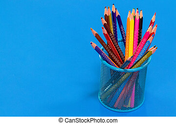 Colored pencils in a pencil case on blue background with copy space