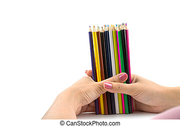 Colored pencils in female hand on white
