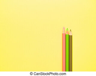 colored pencils lie on a yellow background.
