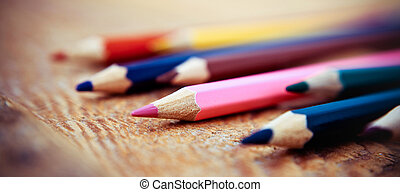 Colored pencils on a wooden background. Vintage