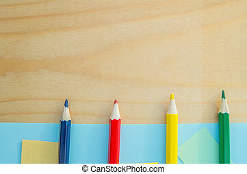 Colored pencils on the bottom edge on a wooden Board top view, back to school
