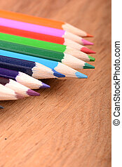 colored pencils on wooden background
