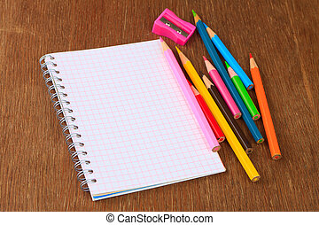 Colored pencils, pencil sharpener and notebook