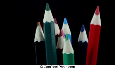 Colored Pencils Rotate on a Black Background