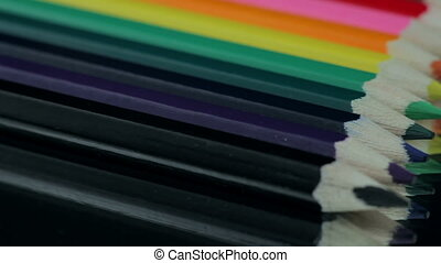 Colored Pencils Rotating on a Black Table.