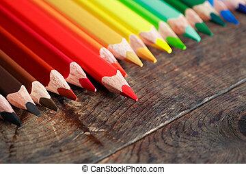 Set of color pencils on old dark wooden surface