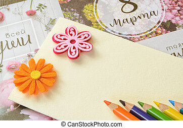 Colored pencils, two stickers for applique in the form of flowers on a blank sheet of a cardboard.