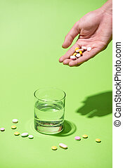 Colored pills in hand with water on blue background.