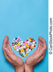 Colored pills in heart shape covered with hands on blue background.