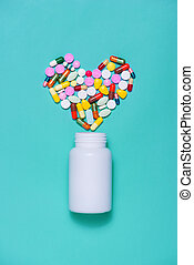 Colored pills in heart shape with bottle on blue background.