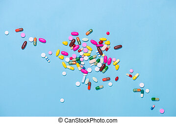 Colored pills on blue background.