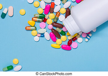 Colored pills with bottle on blue background.