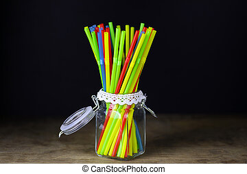 colored plastic cocktail tubes standing in a glass