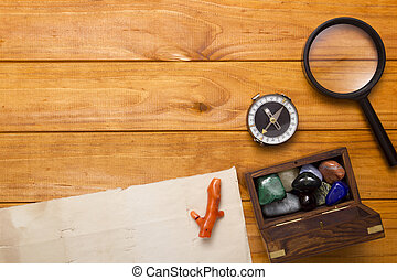 Colored Semi Precious Stones, magnifying glass on a wooden...