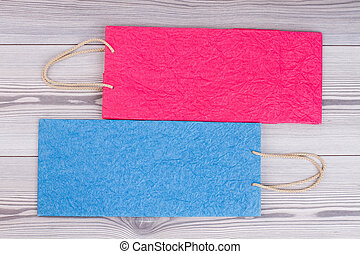 Colored shopping bags on wooden background.