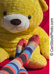 Colored socks on teenager feet isolated on black background