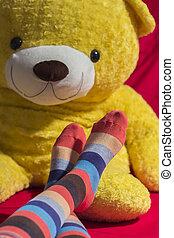 Colored socks on teenager feet isolated on black background
