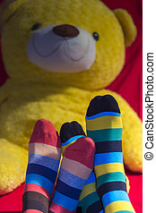 Colored socks on Valentine couple feet with a teddy bear on background