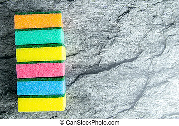 Colored sponges for the kitchen on the background of the table in the color of white marble. Top views with clear space