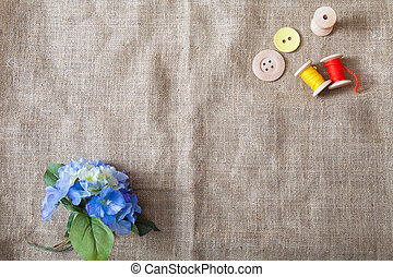 colored threads and buttons and a flower lie on a sackcloth in the corner of the frame