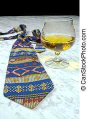 Colored tie with a glass of brandy on the marble table