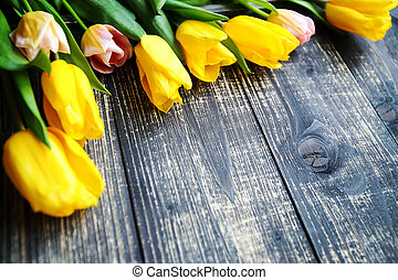Colored tulips on dark wooden background. Easter card.