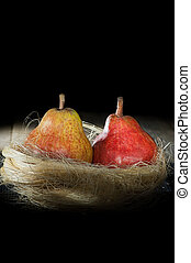 colored two ripe pears on a black background in a yellow socket