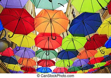 Colored umbrellas hanging at the top. Set of different umbrellas. Local landmark
