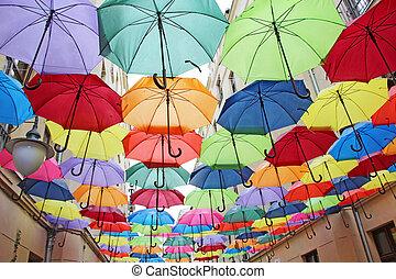 Colored umbrellas hanging at the top. Set of different umbrellas. Local landmark. Multicolored umbrellas. Street decoration. Colored design of exterior