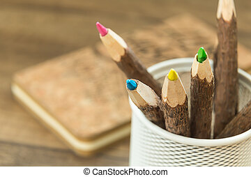 colored wooden pencils in metal office pencil holder