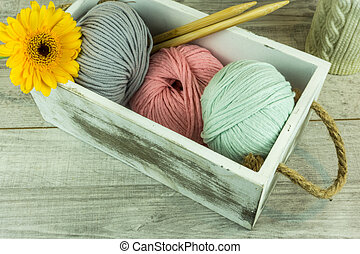 Colored wool ball in a wooden box with needles
